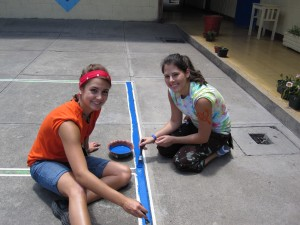 Jordyn and Ceciia painting lines on basketball court